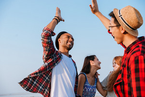 Cheerful young friends laughing and giving high five outdoors
