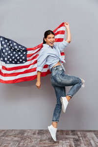 Cheerful young happy girl holding USA flag and jumping over gray background