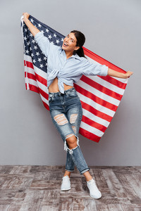 Cheerful young happy girl holding USA flag over gray background