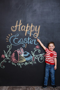 Cheerful young kid standing and pointing at the happy easter sign over chalk blackboard