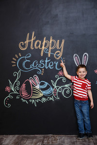 Cheerful young kid wearing bunny ears standing and pointing at the happy easter sign over chalk blackboard