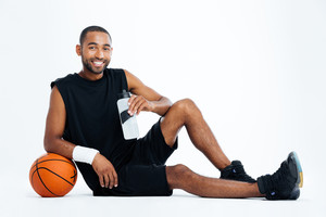 Cheerful young man basketball player sitting and drinking water over white background