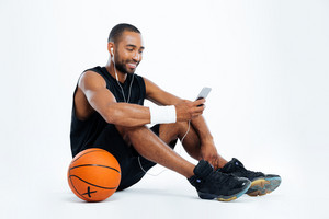 Cheerful young man basketball player sitting and listening to music from mobile phone over white background