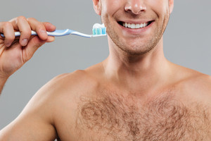 Cheerful young man cleaning teeth with toothbrush and toothpaste and smiling