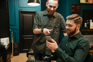 Cheerful young man getting haircut by hairdresser while sitting in chair. Holding phone.