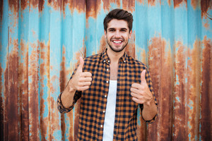 Cheerful young man in checkered shirt standing and showing thumbs up over blue metal background with rust