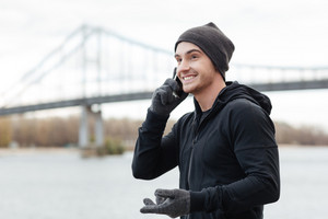 Cheerful young man in hat and gloves standing and talking on cell phone outdoors