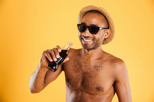 Cheerful young man in hat and sunglasses drinking coke over orange background