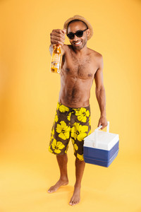 Cheerful young man in hat and sunglasses holding beer bottle and cooler bag over orange background