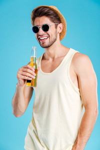 Cheerful young man in hat and sunglasses standing and drinking beer over blue background