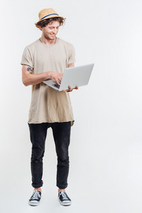 Cheerful young man in hat standing and using laptop over white background