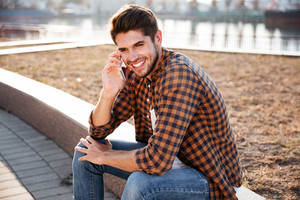 Cheerful young man in plaid shirt sitting and talking on cell phone outdoors
