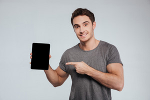 Cheerful young man pointing finger at blank screen tablet over grey background