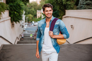 Cheerful young man with backpack enjoying walk the city
