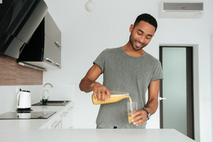 Cheerful young man with glass of juice standing in the kitchen. Look at juice.