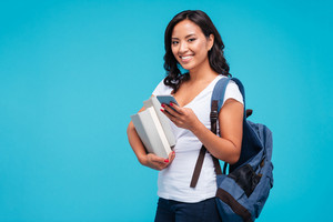 Cheerful young vietnamese girl holding backpack and books using smartphone isolated on a blue background