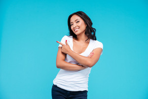 Cheerful young vietnamese girl pointing finger away at copyspace isolated on blue background