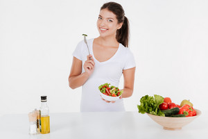 Cheerful young woman cooking with and vegetables. Isolated on white background.