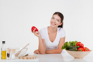 Cheerful young woman cooking with vegetables. Isolated on white background.