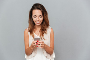 Cheerful young woman holding mobile phone isolated on a gray background