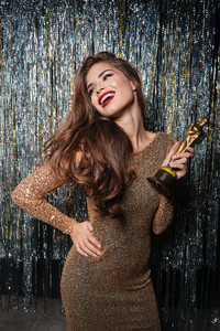 Cheerful young woman in evening dress holding award and laughing over shining background