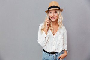 Cheerful young woman in hat talking on mobile phone isolated on a gray background
