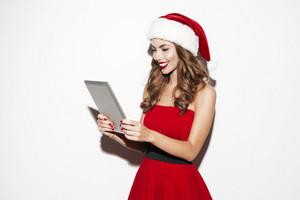 Cheerful young woman in santa claus costume standing and using tablet