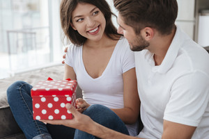 Cheerful young woman taking present from her boyfriend at home