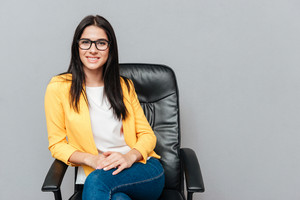Cheerful young woman wearing eyeglasses and dressed in yellow jacket sitting on office chair over grey background.