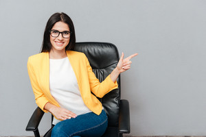 Cheerful young woman wearing eyeglasses and dressed in yellow jacket sitting on office chair while pointing over grey background.