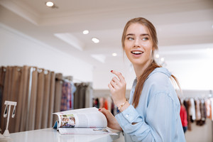 Cheerful young woman with fashion magazine standing and laughing in clothes shop