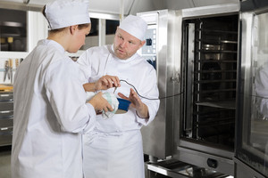 Chef helps student with cooking in a large kitchen