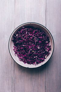 Chopped purple cabbage in a bowl on the table top view, vertical framing