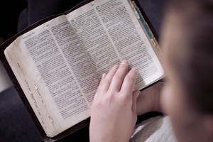 Christian girl reading the holy bible at home. Sitting in sofa.