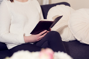 Christian woman or girl reading the holy bible at home.