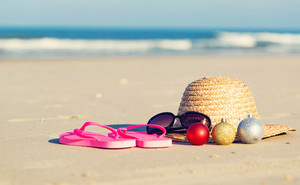 Christmas baubles with straw hat and sunglasses on a tropical beach
