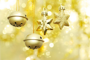 Christmas bells and stars hanging over golden bokeh background