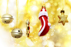 Christmas bells, glove and stars hanging over golden bokeh background