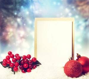Christmas card with red ornaments on the snow