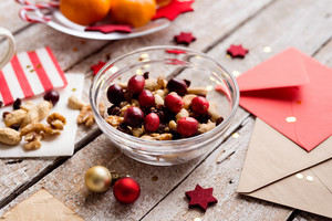 Christmas composition. Bowl with dried fruit, cranberries and nuts. Christmas cards and decorations. Various objects laid on table. Studio shot, wooden background.