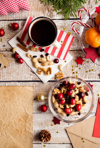 Christmas composition. Bowl with dried fruit, cranberries and nuts. Cup of coffee. Christmas decorations. Various objects laid on table. Studio shot, wooden background. Copy space.