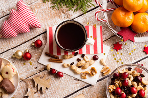 Christmas composition. Cup of coffe, bowl with dried fruit, cranberries and nuts, tangerines on plate. Various objects laid on table. Studio shot, wooden background.