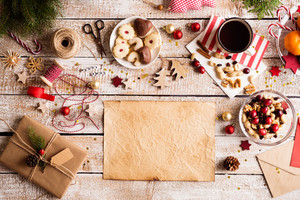 Christmas composition. Empty old sheet of paper. Dried fruit and nuts. Cup of coffee. Jelly cookies on plate. Christmas decorations. Various objects laid on table. Studio shot, wooden background. Copy space.