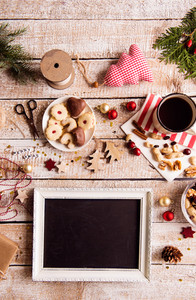 Christmas composition. Picture frame. Dried fruit, cranberries and nuts. Cup of coffee and cookies. Various objects laid on table. Studio shot, wooden background. Copy space.