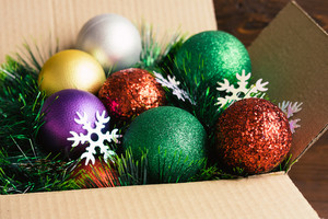 Christmas decoration in a cardboard box on a wooden background closeup
