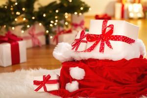 Christmas gift boxes in Santas sack on a white carpet at night