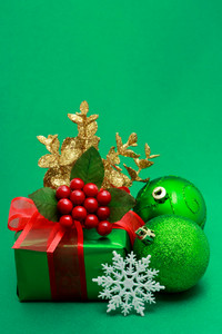 Christmas green gift box with ornaments on green background