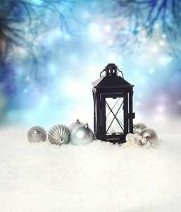 Christmas lantern and ornaments on the snow in a blue shinning night