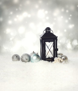 Christmas lantern and ornaments on the snow in a silver shinning night