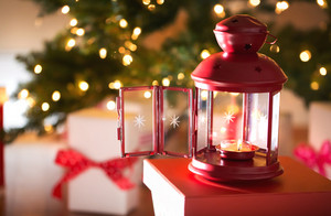 Christmas lantern with gift boxes under tree at night